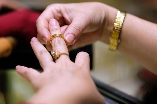 Una mujer se prueba anillos de oro en una joyería.