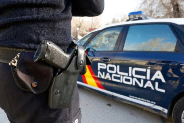 Un agente de la Policía Nacional junto a su vehículo.