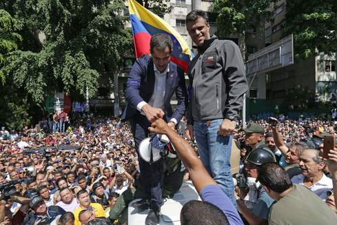 "Venezuelan opposition leader and self-proclaimed acting president Juan Guaido (L) and high-profile opposition politician Leopoldo Lopez, who had been put under home arrest by Venezuelan President Nicolas Maduro's regime, greet supporters after being joined by members of the Bolivarian National Guard to oust Maduro, in Caracas on April 30, 2019. - Guaido -- accused by the government of attempting a coup Tuesday -- said there was ""no turning back"" in his attempt to oust President Nicolas Maduro from power. (Photo by Cristian <HIT>HERNANDEZ</HIT> / AFP)"