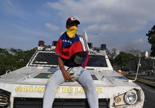 Un manifestante se sienta en una de las tanquetas de la Guardia Nacional Bolivariana.