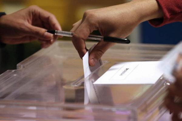 Una persona deposita su voto en la urna de un colegio de Madrid el...