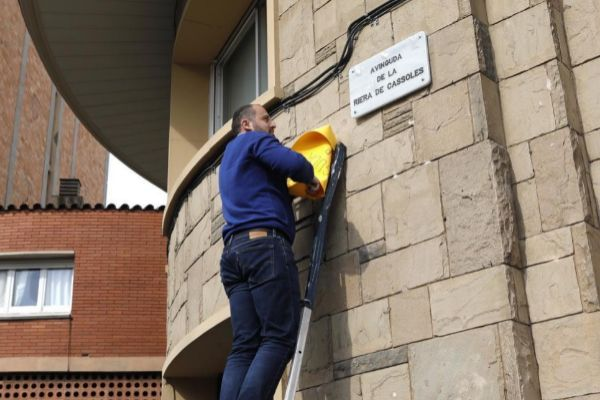Un operario cambio una placa del nomenclator para cambiar el nombre de la avenida Príncipe de Asturia en Barcelona, ahora passatge de Cassoles.