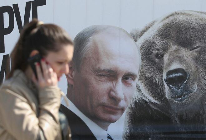 Un mujer pasa junto a un mural en el que Vladimir Putin guiña un ojo.
