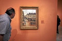 "Un visitante observa ""Rue Saint-Honoré, efecto lluvia"", de Camille Pissarro."