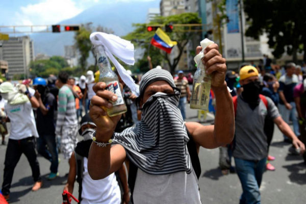 Un manifestante muestra un cóctel molotov.