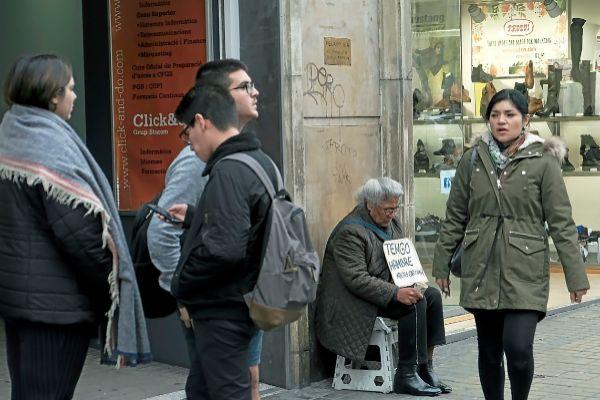 Transeúntes en una céntrica calle comercial de Barcelona donde también se instalan personas necesitadas pidiendo limosna. JORDI SOTERAS
