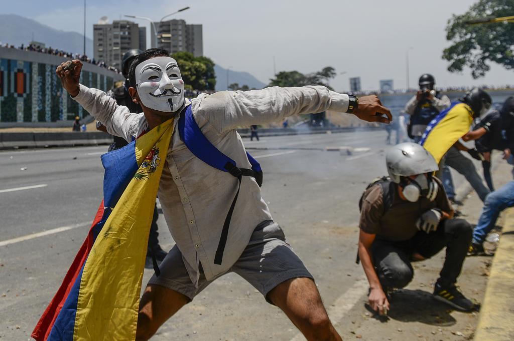 Un opositor venezolano lanza una piedra durante una protesta.