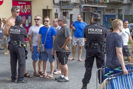 Un agente de Policía Nacional atiende a unos turistas en Benidorm.