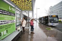 Varias personas esperan en una parada la llegada del autobús.