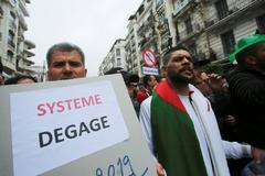 Demonstrators hold flags and banners demanding the departure of <HIT>Algeria</HIT>'s ruling elite, a month after the downfall of President Abdelaziz Bouteflik, during an anti-government protest in Algiers