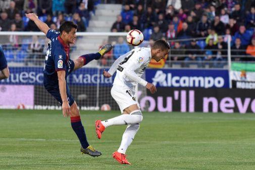 Rodrigo pugna por un balón con el defensa del Huesca Martín Mantovani.