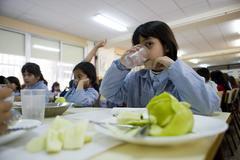 Varios niñós en un comedor escolar.
