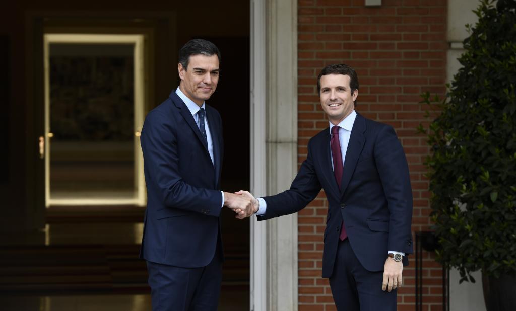 Pedro Sánchez y Pablo Casado se estrechan la mano antes de su reunión.