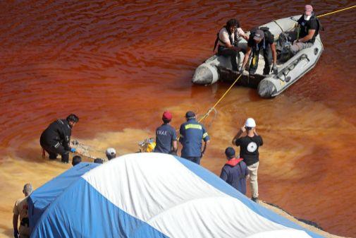 Los equipos de búsqueda sacan la maleta del lago.