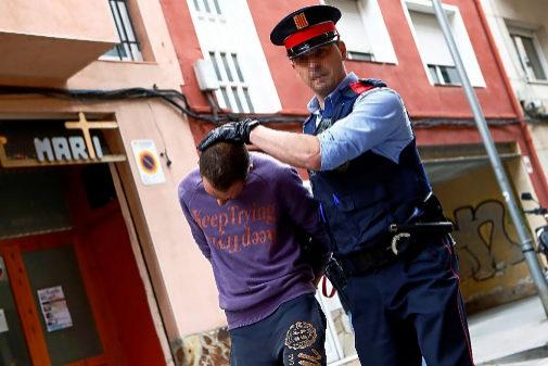Un agente de los Mossos detiene a uno de los sospechosos