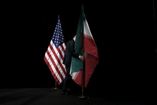 Un miembro del personal retira la bandera iraní del escenario...