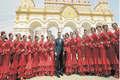 El presidente de la Junta, Juan Manuel Moreno, posa junto a un grupo de mujeres 'uniformadas' con traje de flamenca en la portada de la Feria.