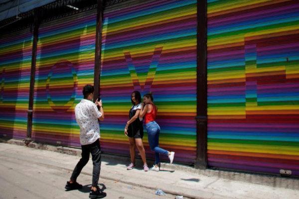 Dos chicas posan para una foto frente a la bandera homosexual en La Habana.