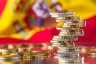 Una pila de monedas y la bandera de España