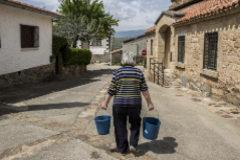 Nieves se dirige con dos cubos de agua hacia su casa para regar las plantas.