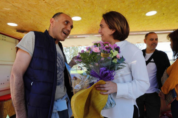 Luca, un fan italiano de Ada Colau, entrega un ramo a la alcaldesa durante un mitin sobre ecología.