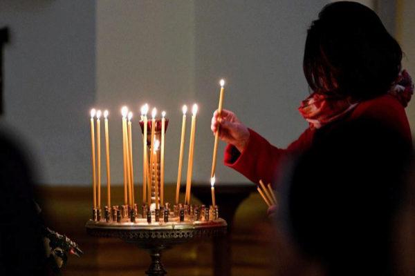 Una mujer enciende una vela en la catedral de  Przemysl (Polonia).