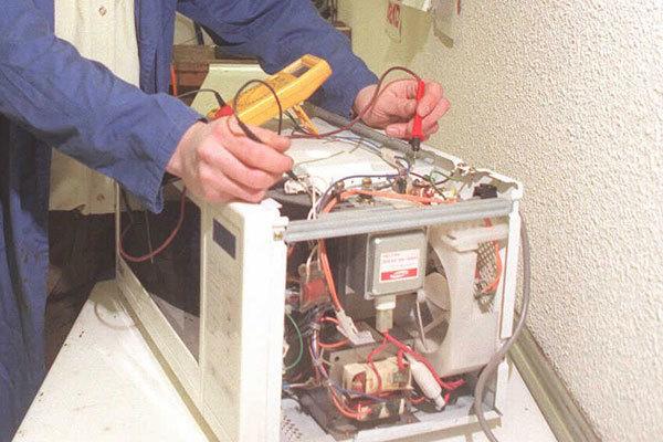 Un operario repara un electrodoméstico.