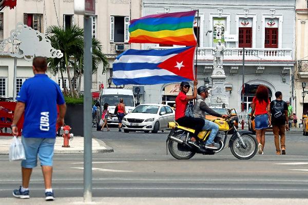 Activistas por los derechos homosexuales recorren una calle de La Habana alzando las banderas cubana y gay, durante la marca del sábado.