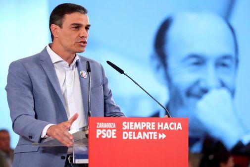 Pedro Sánchez, en un acto de campaña con una foto de Rubalcaba
