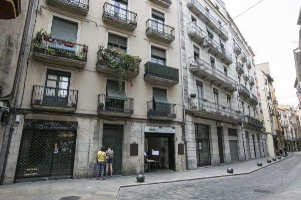 Una pareja de turistas accediendo a un bloque con apartamentos turísticos, en el centro de Girona.