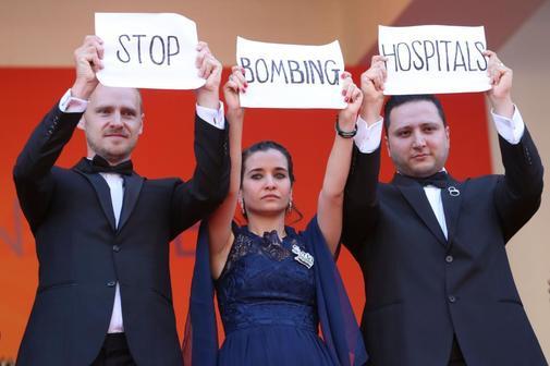 """Unos asistentes a la gala de 'Les Misérables' muestran el cartel """"Stop a los bombardeos de hospitales'."""