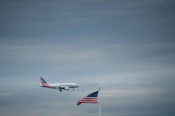 Un avión de American Airlines pasa cerca de una bandera americana