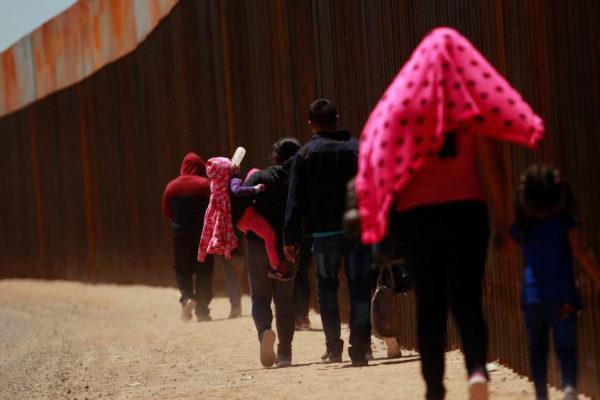 Varias personas caminan por la valla fronteriza entre Estados Unidos y México, en El Paso.