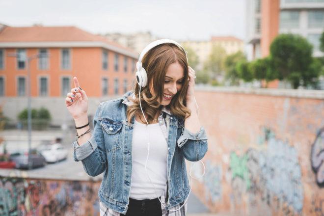 Una chica joven escucha música con unos auriculares.