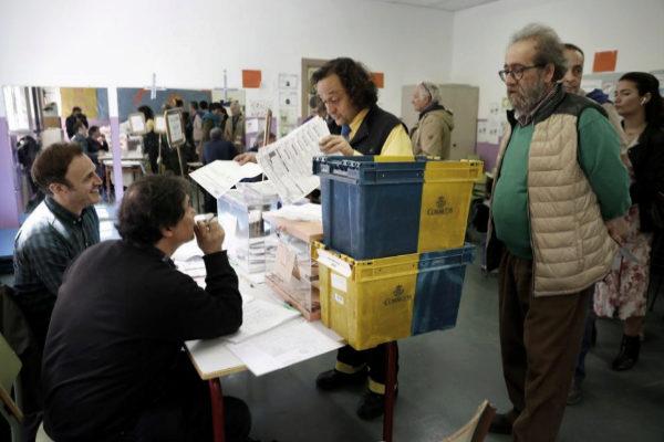 Un empleado de Correos entrega los votos en una mesa electoral durante...