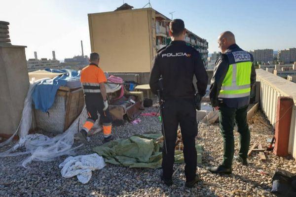 Agentes de la policía inspeccionando el campamento localizado en la terraza de un bloque de La Mina.