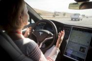 Una mujer prueba el piloto automático de un modelo de Tesla.