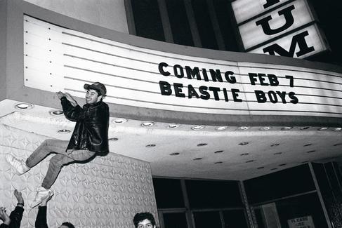 Adam 'MCA' Yauch colgado de un letrero que anuncia un concierto de Beastie Boys.