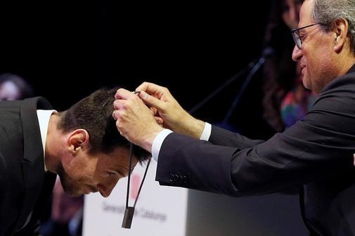 Torra coloca la condecoración a Messi.
