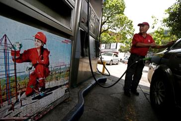 A worker pumps fuel into a vehicle at a state oil company PDVSA's gas station in Caracas