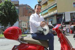 El alcaldable del PP Manu Reyes posa con su Vespa roja en la plaza de España de Castelldefels.