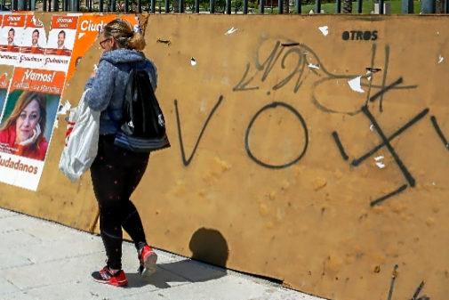 Una mujer pasa ante una pintada de Vox en Seseña