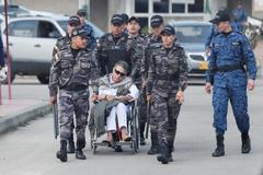 Miembros del Cuerpo Técnico de Investigación acompañan la salida del ex jefe guerrillero.