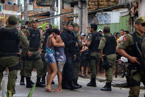 Dos mujeres se abrazan, rodeadas de policías, frente al bar donde ocurrió la matanza en Belém.