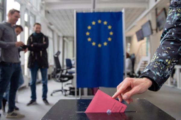 Una electora de Hamburgo deposita en una urna su voto por correo para las elecciones al Parlamento Europeo.