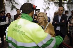 La alcaldesa de Madrid habla con un trabajador municipal con el delegado de Urbanismo de fondo.