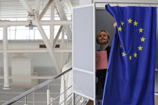 na votante entra en una cabina de votación para cumplimentar su voto por correo en las elecciones europeas