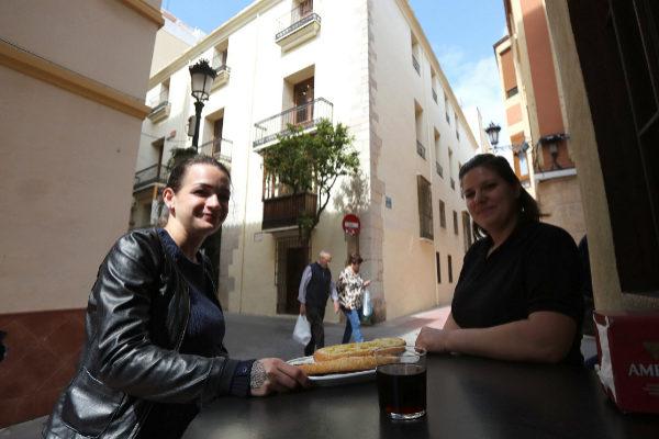 Dos jóvenes almuerzan en La Bona Vida, frente al Museo Etnológico.