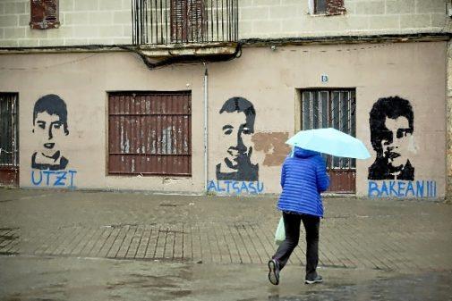 Una vecina pasa ante un fachada con pintadas de los presos de Alsasua