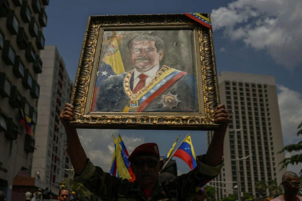 Un simpatizante de Maduro levanta un cuadro con su imagen en una marcha en Caracas.